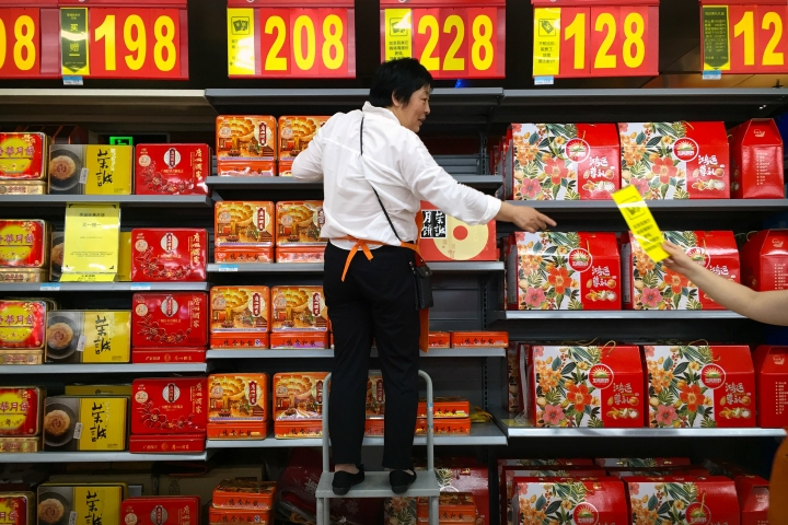 An employee stands on a stepladder as she stocks boxes of mooncakes at a supermarket in Beijing, Wednesday, Sept. 14, 2016. Four employees at Chinese internet giant Alibaba have lost their jobs after being accused of reprogramming an internal system to steal more than 100 boxes of mooncakes, a traditional delicacy shared during this week's Mid-Autumn Festival. (AP Photo/Mark Schiefelbein)