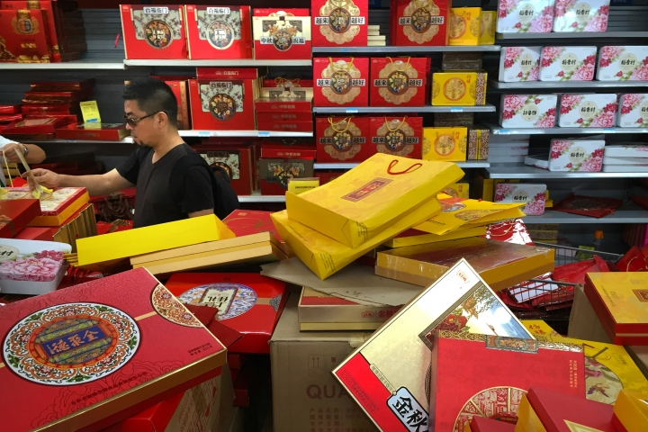 A customer shops for boxes of mooncakes at a supermarket in Beijing, Wednesday, Sept. 14, 2016. Four employees at Chinese internet giant Alibaba have lost their jobs after being accused of reprogramming an internal system to steal more than 100 boxes of mooncakes, a traditional delicacy shared during this week's Mid-Autumn Festival. (AP Photo/Mark Schiefelbein)