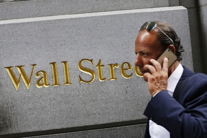 FILE - In this Monday, July 6, 2015, file photo, a man uses a mobile phone while walking by a building in the Financial District in New York. U.S. stocks are slightly higher in early trading Wednesday, Sept. 14, 2016, as utility companies climb. Energy companies are trading lower as the price of oil continues to slip. Stocks are at their lowest levels in two months after large losses in two of the previous three days. (AP Photo/Mark Lennihan, File)