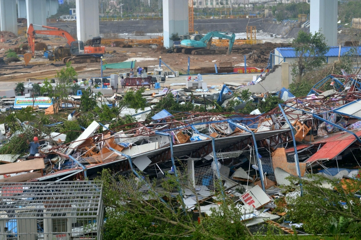 A man wearing a red helmet, left, climbs on the wreckage of a destroyed structure after a typhoon in Xiamen in southeastern China's Fujian province Thursday, Sept. 15, 2016. Typhoon Meranti, labeled the strongest storm so far this year by Chinese and Taiwanese weather authorities, made landfall in southeastern China early Thursday after previously affecting Taiwan. (Chinatopix via AP)