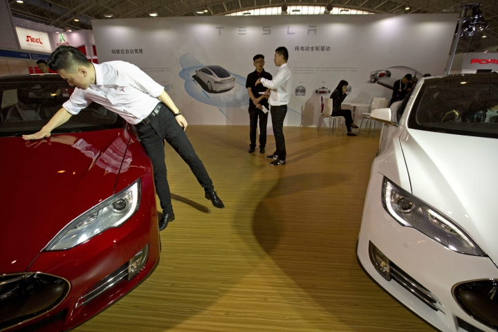 FILE - In this Monday, April 25, 2016, file photo, a staff member cleans the hood of a Tesla Model S electric car near a display advertising Tesla's self-driving features at the Beijing International Automotive Exhibition in Beijing, China. Tesla says it can't verify whether a vehicle autopilot system is to blame for the death of a Chinese man whose father claimed in a report broadcasted Wednesday, Sept. 14, 2016, on state television that the driver-assist feature was active at the time of his crash. (AP Photo/Mark Schiefelbein, File)