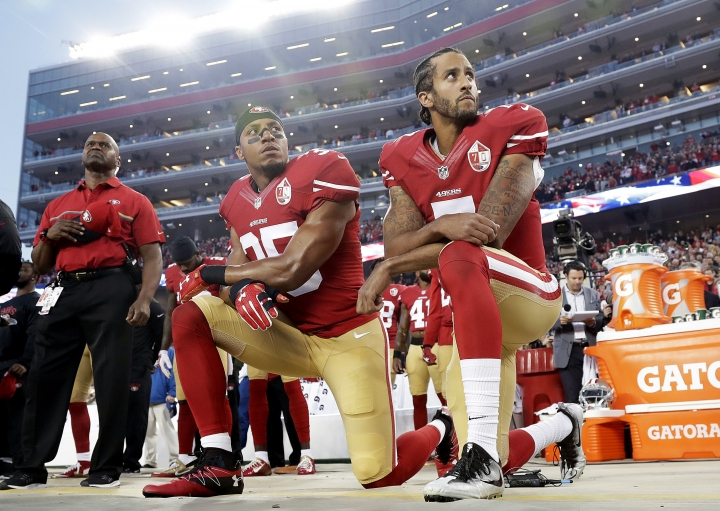FILE - Int his Monday, Sept. 12, 2016, file photo, San Francisco 49ers safety Eric Reid (35) and quarterback Colin Kaepernick (7) kneel during the national anthem before an NFL football game against the Los Angeles Rams in Santa Clara, Calif. The dozen NFL players who have joined Kaepernick's protest of social injustices by kneeling or raising a fist during the national anthem have faced vitriolic, sometimes racist reactions on social media and at least one has lost endorsements. None are deterred by the backlash. (AP Photo/Marcio Jose Sanchez, File)
