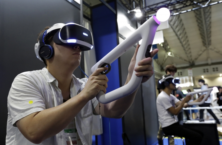 A visitor tries out a PlayStation VR headgear device at the Tokyo Game Show in Makuhari, near Tokyo, Thursday, Sept. 15, 2016. Virtual reality has arrived for real at the Tokyo Game Show, one of the world's biggest exhibitions for the latest in fun and games. (AP Photo/Eugene Hoshiko)