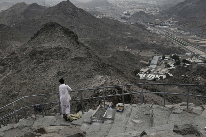 In this Friday, Sept. 9, 2016 photo, a Pakistani man, who makes steps out of cement, takes in the view from Noor Mountain, where Prophet Muhammad received his first revelation from God to preach Islam, on the outskirts of Mecca, Saudi Arabia. Unlike the quiet and seemingly endless stretch of nature the prophet would have seen from the cave, massive high-rise towers housing five-star hotels hover in the distant skyline just steps away from the cube-shaped Kaaba, Islam's holiest site. The Pakistani workers and beggars who live off the mountain's draw say they play a key role in helping to preserve it.(AP Photo/Nariman El-Mofty)