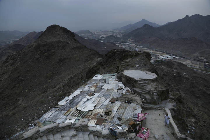 In this Friday, Sept. 9, 2016 photo, Pakistani men live near Hira cave on Noor Mountain, where Prophet Muhammad received his first revelation from God to preach Islam, on the outskirts of Mecca, Saudi Arabia. Unlike the quiet and seemingly endless stretch of nature the prophet would have seen from the cave, massive high-rise towers housing five-star hotels hover in the distant skyline just steps away from the cube-shaped Kaaba, Islam's holiest site. The Pakistani workers and beggars who live off the mountain's draw say they play a key role in helping to preserve it. (AP Photo/Nariman El-Mofty)