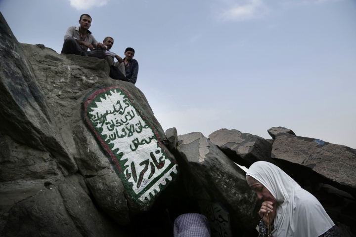 In this Friday, Sept. 9, 2016 photo, a Turkish Muslim woman prays outside Hira cave, where Prophet Muhammad received his first revelation from God to preach Islam, at Noor Mountain, on the outskirts of Mecca, Saudi Arabia. Arabic is from the first verse of the Quran. (AP Photo/Nariman El-Mofty)