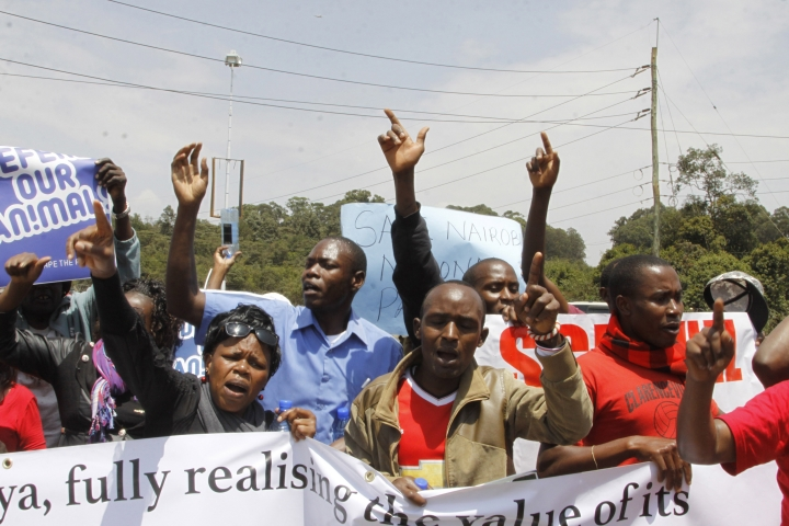 "Kenyans hold up signs as they attend a protest to protect the Nairobi National Park in Nairobi, Friday, Sept. 16, 2016. Dozens of angry people have marched in the Kenyan capital Nairobi to protest plans to build a railway line over a national park. The protesters included conservationists and others who wore T-shirts and carried banners saying ""don't rape our park."" (AP Photo/Khalil Senosi)"