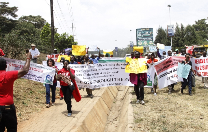 "Kenyan citizens attend a protest to protect the Nairobi National Park in Nairobi, Friday, Sept. 16, 2016. Dozens of angry people have marched in the Kenyan capital Nairobi to protest plans to build a railway line over a national park. The protesters included conservationists and others who wore T-shirts and carried banners saying ""don't rape our park."" (AP Photo/Khalil Senosi)"