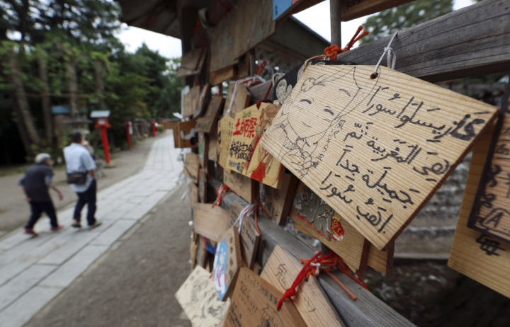 "Visitors walk by pictorial offerings including one hanged by a foreign visitor at Washinomiya Jinja shrine in Kuki, Saitama prefecture, north of Tokyo, Friday, Sept. 16, 2016. Eighty-eight places in Japan are going to be designated ""animation spots"" to encourage tourism — using train stations, school campuses, rural shrines and other fairly everyday places where popular ""manga"" characters are depicted. One shoo-in for the list, according to organizers, is Washinomiya Jinja, a picturesque shrine, which is a familiar scene in the comic by Kagami Yoshimizu, which later became a TV animation series, ""Lucky Star"" or ""Raki Suta."" (AP Photo/Eugene Hoshiko)"