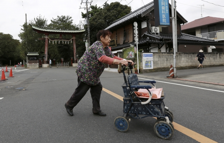 """An elderly woman crosses a street with a walker in front of a torii gate of Washinomiya Jinja shrine in Kuki, Saitama prefecture, north of Tokyo, Friday, Sept. 16, 2016. Eighty-eight places in Japan are going to be designated """"animation spots"""" to encourage tourism — using train stations, school campuses, rural shrines and other fairly everyday places where popular """"manga"""" characters are depicted. One shoo-in for the list, according to organizers, is Washinomiya Jinja, a picturesque shrine, which is a familiar scene in the comic by Kagami Yoshimizu, which later became a TV animation series, """"Lucky Star"""" or """"Raki Suta."""" (AP Photo/Eugene Hoshiko)"""