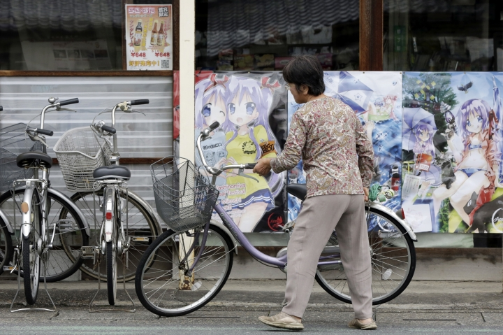 "A woman moves her bicycle near posters featuring the characters of a popular TV animation series, ""Lucky Star"" or ""Raki Suta"" near Washinomiya Jinja shrine in Kuki, Saitama prefecture, north of Tokyo, Friday, Sept. 16, 2016. Eighty-eight places in Japan are going to be designated ""animation spots"" to encourage tourism — using train stations, school campuses, rural shrines and other fairly everyday places where popular ""manga"" characters are depicted. One shoo-in for the list, according to organizers, is Washinomiya Jinja, a picturesque shrine, which is a familiar scene in the comic by Kagami Yoshimizu, which later became the TV animation series. (AP Photo/Eugene Hoshiko)"