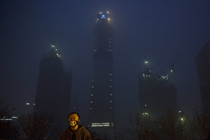 A man wears a mask with a skeleton design near the smoggy night scene of the Central Business District under construction in Beijing, China, Wednesday, Dec. 21, 2016. Chinese weather forecasters and state media say the dense, gray smog that has smothered much of China, closing schools and grounding planes, may finally soon give way. (AP Photo/Ng Han Guan)