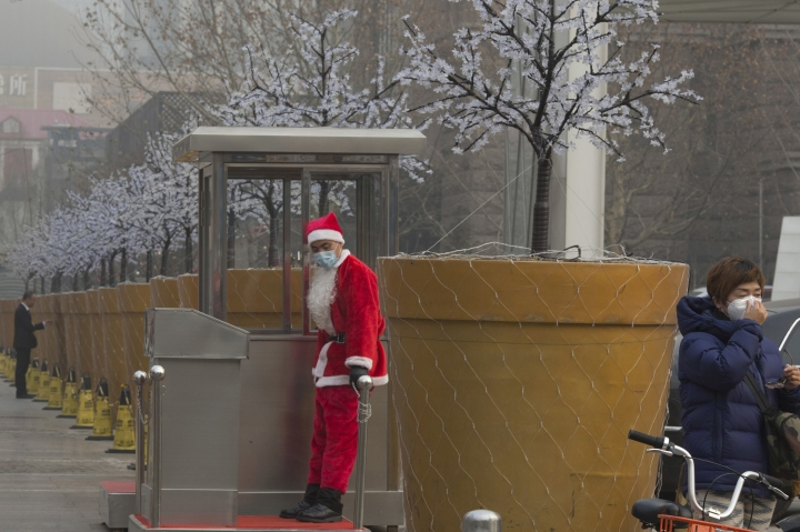 "A carpark attendant dressed as Santa Claus wears a mask during a hazy day in Beijing, China, Wednesday, Dec. 21, 2016. Beijing and much of industrial northern China are in the midst of a ""red alert,"" the highest level in China's four-tiered pollution warning system. The alert has affected 460 million people, according to Greenpeace East Asia, which calculated that about 200 million people were living in areas that had experienced levels of air pollution more than 10 times above the guideline set by the World Health Organization. (AP Photo/Ng Han Guan)"