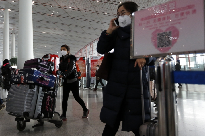 """People wearing masks for protection against air pollution push their luggage at the Beijing Capital International Airport as the capital of China is shrouded by heavy smog on Wednesday, Dec. 21, 2016. Beijing and much of industrial northern China are in the midst of a """"red alert,"""" the highest level in China's four-tiered pollution warning system. The alert has affected 460 million people, according to Greenpeace East Asia, which calculated that about 200 million people were living in areas that had experienced levels of air pollution more than 10 times above the guideline set by the World Health Organization. (AP Photo/Andy Wong)"""