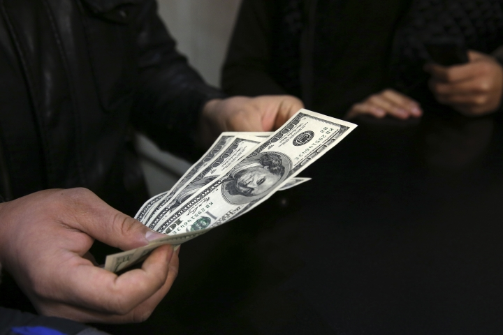 In this picture taken on Monday, Dec. 26, 2016, a customer counts U.S. dollars in a currency exchange bureau in downtown Tehran, Iran. Iran's currency has struck an all-time low this week, trading at 41,600 rials to $1. While making Iranian exports more attractive to the world market in the wake of the nuclear deal, it also means people's savings continue to lose value in the Islamic Republic. Meanwhile, concerns gather about what U.S. President-elect Donald Trump might mean for the atomic accord going forward, even as most Iranians have yet to feel any change from it.(AP Photo/Vahid Salemi)