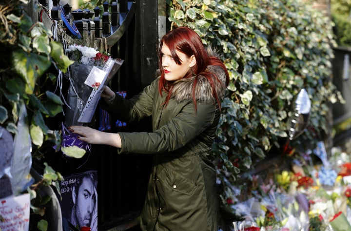 A woman hangs flowers at the entrance gate outside the home of British musician George Michael in London, Tuesday, Dec. 27, 2016. George Michael, who rocketed to stardom with WHAM! and went on to enjoy a long and celebrated solo career lined with controversies, has died, his publicist said Sunday. He was 53.(AP Photo/Frank Augstein)