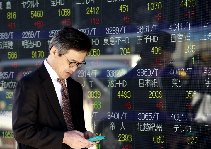 A man uses a mobile phone in front of an electronic stock indicator of a securities firm in Tokyo, Wednesday, Dec. 28, 2016. Shares meandered in quiet trading in Asia on Wednesday after the Dow Jones industrial average inched closer to 20,000 and the Nasdaq Composite rose to a record high. (AP Photo/Shizuo Kambayashi)