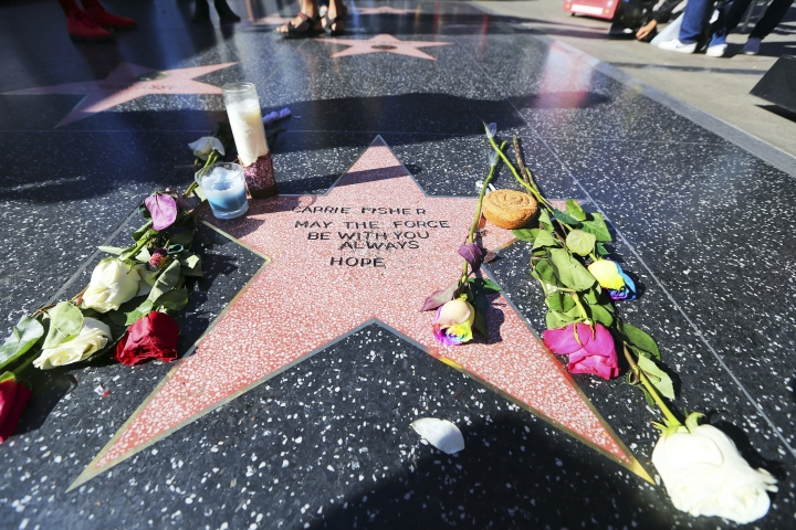 """Flowers and candles adorn an impromptu memorial created on a blank Hollywood Walk of Fame star by fans of late actress and author Carrie Fisher, who does not have an official star on the world-famous promenade, in Los Angeles Wednesday, Dec. 28, 2016. Paste-on letters spell out her name and the phrase """"May the force be with you always. Hope."""" (AP Photo/Reed Saxon)"""