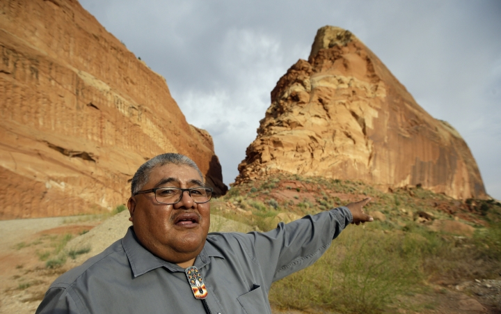 """FILE - This June 21, 2016, file photo, Malcolm Lehi, a Ute Mountain Tribal Commissioner points to a rock formation near Blanding, Utah. """"We don't want to forget about our ancestors,"""" said Lehi. """"Through them we speak. That's the whole concept of protecting and healing this land. They are still here among us as the wind blows."""" President Barack Obama designated two national monuments Wednesday, Dec. 28, at sites in Utah and Nevada that have become key flashpoints over use of public land in the U.S. West. (AP Photo/Rick Bowmer, File)"""