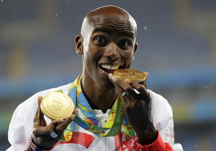 FILE - In this file photo dated Saturday, Aug. 20, 2016, Britain's Mo Farah poses with his gold medals after winning the men's 5000-meter event, during the 2016 Summer Olympics in Rio de Janeiro, Brazil. Four-time Olympic gold medallist Farah is awarded a Knighthood in the Queen's 2017 New Year Honors. (AP Photo/Jae C. Hong, FILE)