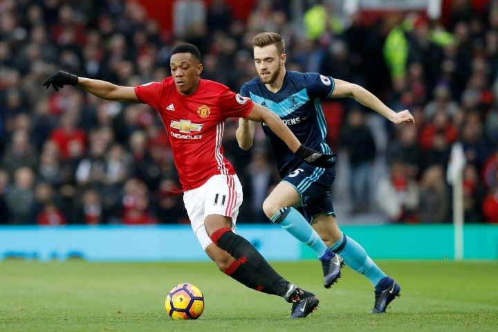 Manchester United's Anthony Martial, left, and Middlesbrough's Calum Chambers battle for the ball during their English Premier League soccer match at Old Trafford, Manchester England Saturday Dec. 31, 2016. (Martin Rickett/PA via AP)