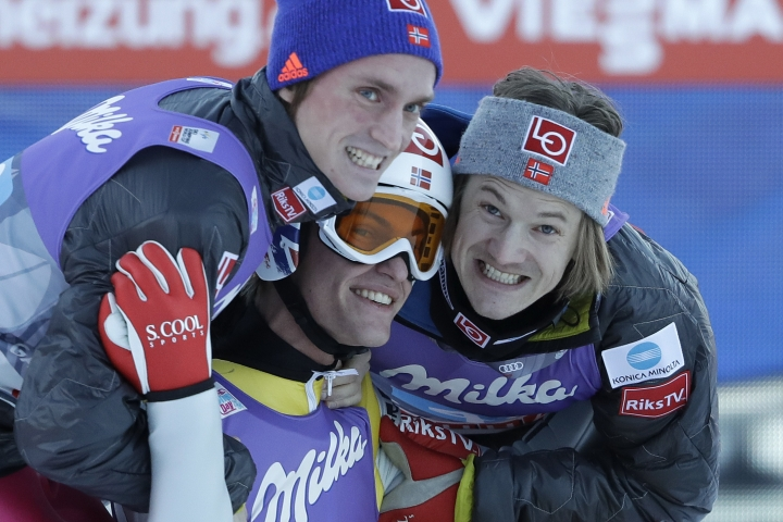 Norway's Daniel Andre Tande, center, celebrates with team mates Tom Hilde, right, and Andreas Stjernen after winning the second stage of the 65th four hills ski jumping tournament in Garmisch-Partenkirchen, Germany, Sunday, Jan. 1, 2017. (AP Photo/Matthias Schrader)