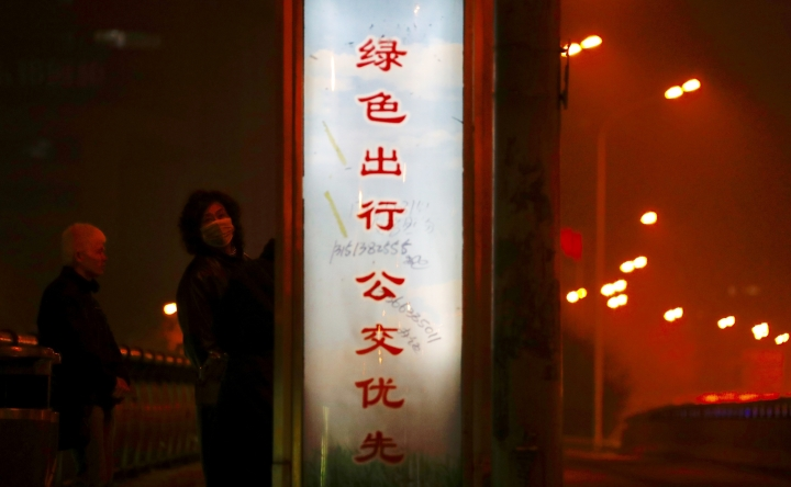 "A pedestrian wearing a mask looks back while passing by a slogan that reads: ""If you want to go out, please take a public bus"" in Beijing Monday, Jan. 2, 2017. Beijing and other cities across northern and central China were shrouded in thick smog Monday, Jan. 2, 2017, prompting authorities to delay dozens of flights and close highways. (AP Photo/Andy Wong)"
