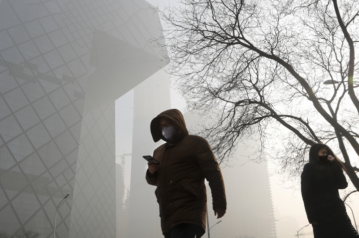 "People wearing protection masks walk near the iconic headquarters of China's state broadcaster Central China Television (CCTV) at the Central Business District in Beijing as the capital of China is blanked by heavy smog on Tuesday, Jan. 3, 2017. China's Ministry of Environment says an unspecified number of companies have violated measures meant to reduce smog as the country deals with a phase of particularly noxious pollution. Beijing has been on ""orange alert"" the second highest pollution alert level since Friday. The alert was originally due to end on Sunday but authorities have extended it a further three days. (AP Photo/Andy Wong)"