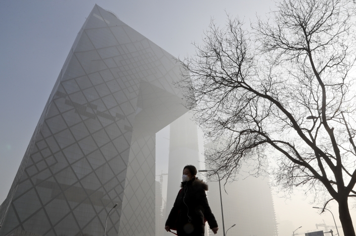 "A Chinese woman wearing a protection mask walks near the iconic headquarters of China's state broadcaster Central China Television (CCTV) at the Central Business District in Beijing as the capital of China is blanked by heavy smog Tuesday, Jan. 3, 2017. China's Ministry of Environment says an unspecified number of companies have violated measures meant to reduce smog as the country deals with a phase of particularly noxious pollution. Beijing has been on ""orange alert"" the second highest pollution alert level since Friday. The alert was originally due to end on Sunday but authorities have extended it a further three days. (AP Photo/Andy Wong)"