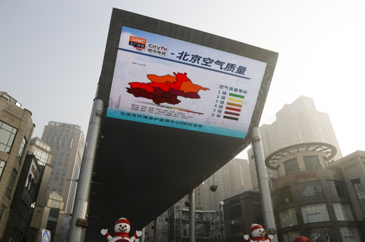 "A huge TV screen shows air quality in Beijing as the capital of China is blanked by heavy smog Tuesday, Jan. 3, 2017. China's Ministry of Environment says an unspecified number of companies have violated measures meant to reduce smog as the country deals with a phase of particularly noxious pollution. Beijing has been on ""orange alert"" the second highest pollution alert level since Friday. The alert was originally due to end on Sunday but authorities have extended it a further three days. (AP Photo/Andy Wong)"