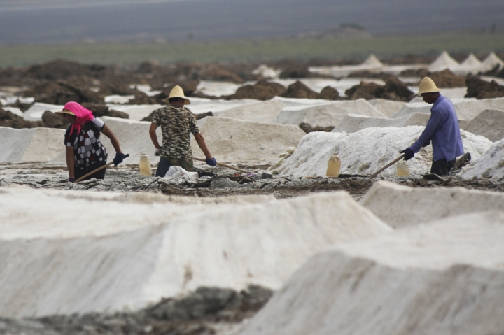 In this Aug. 13, 2011 photo, migrant workers shovel raw salt at the Qijiaojing Salt Field in Hami in northwest China's Xinjiang Uygur Autonomous Region. China has started an overhaul of its salt industry, easing a monopoly that has existed in some form for more than 2,000 years and predates the Great Wall. (Chinatopix via AP)