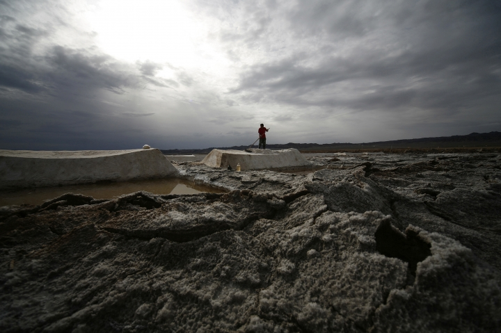 In this Aug. 13, 2011 photo, a worker shovels raw salt at the Qijiaojing Salt Field in Hami in northwest China's Xinjiang Uygur Autonomous Region. China has started an overhaul of its salt industry, easing a monopoly that has existed in some form for more than 2,000 years and predates the Great Wall. (Chinatopix via AP)