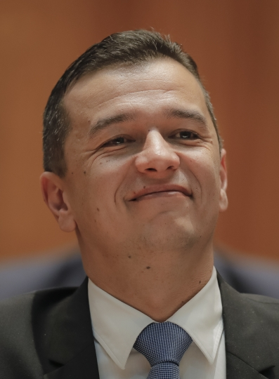 """Romanian Prime Minister designate Sorin Grindeanu smiles, prior to a parliament session, in Bucharest, Romania, Wednesday, Jan. 4, 2017. Grindeanu said Wednesday he wants to stop thousands of Romanians emigrating, build highways and encourage the consumption of local produce to create what he called """"a normal Romania."""" (AP Photo/Vadim Ghirda)"""