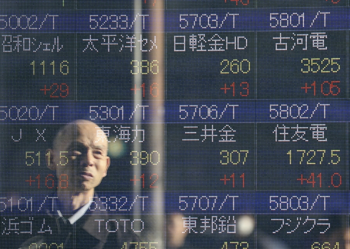 A man is reflected on the electronic board of a securities firm in Tokyo,Wednesday, Jan. 4, 2017. Asian shares were mixed Wednesday, as the Tokyo benchmark jumped in the first trading of 2017, helped by a weak yen. Other indexes lost some gains from earlier this week. (AP Photo/Koji Sasahara)