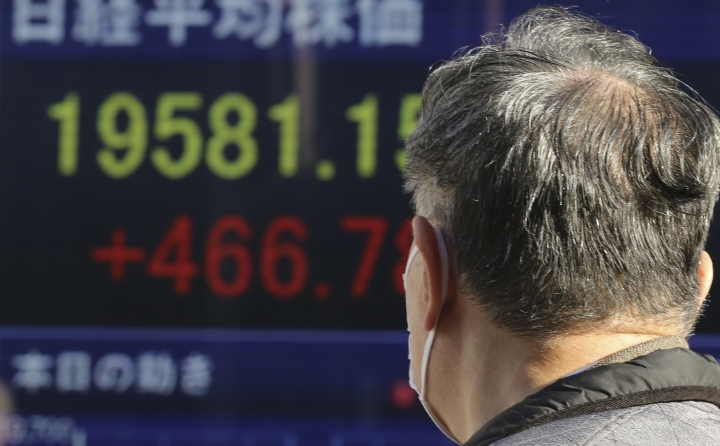 A man looks at an electronic stock board of a securities firm in Tokyo, Wednesday, Jan. 4, 2017. Asian shares were mixed Wednesday, as the Tokyo benchmark jumped in the first trading of 2017, helped by a weak yen. Other indexes lost some gains from earlier this week. (AP Photo/Koji Sasahara)