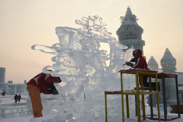 In this Jan. 3, 2017, photo, released by Xinhua News Agency, contestants carve an ice sculpture during an international ice sculpture contest during the Harbin Ice and Snow festival in Harbin, capital of northeast China's Heilongjiang Province. The city of Harbin in China's frigid northeast is in its final stages of preparation for one of the world's largest ice and snow festivals, an annual event that last year drew more than a million visitors. (Wang Jianwei/Xinhua via AP)