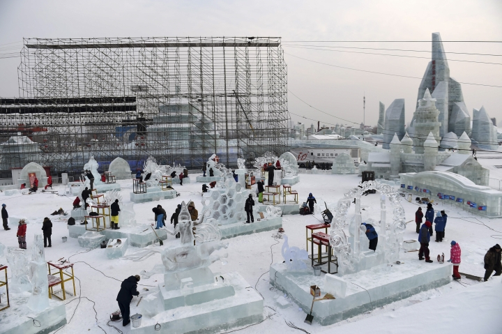 In this Jan. 3, 2017, photo, released by Xinhua News Agency, contestants carve ice sculptures during an international ice sculpture contest as part of the Harbin Ice and Snow festival in Harbin, capital of northeast China's Heilongjiang Province. The city of Harbin in China's frigid northeast is in its final stages of preparation for one of the world's largest ice and snow festivals, an annual event that last year drew more than a million visitors. (Wang Jianwei/Xinhua via AP)