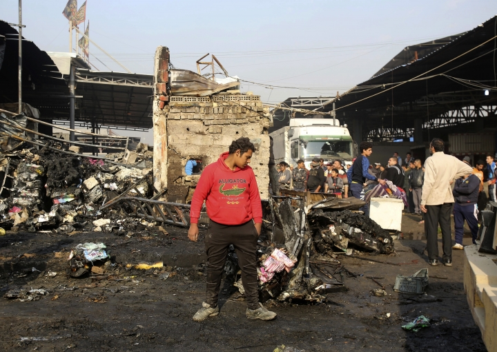 Citizens inspect the scene after a car bomb explosion at a crowded outdoor market in the Iraqi capital's eastern district of Sadr City, Iraq, Sunday, Jan 8, 2017. An Iraqi official says a suicide bombing in a bustling commercial area in the Iraqi capital has killed several civilians. (AP Photo/ Karim Kadim)