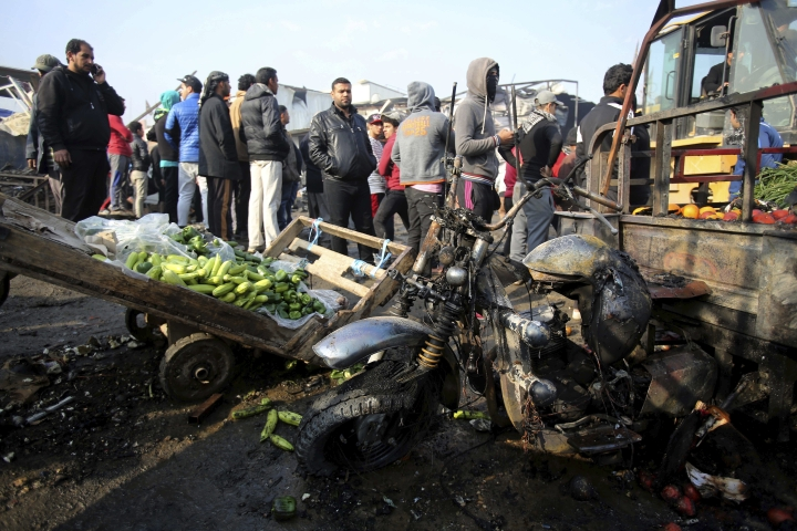 Citizens inspect the scene after a car bomb explosion at a crowded outdoor market in the Iraqi capital's eastern district of Sadr City, Iraq, Sunday, Jan 8, 2017. An Iraqi official says a suicide bombing in a bustling commercial area in the Iraqi capital has killed several civilians (AP Photo/ Karim Kadim)