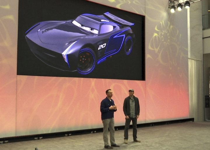 """In an image from video, Pixar Animation Studios Creative Director Jay Ward, left and Prodction Designer Jay Shuster, unveil an aggressive newcomer to Disney Pixar's """"Cars"""" series named Jackson Storm during a news conference at the North American International Auto Show, Sunday, Jan. 8, 2017 in Detroit. The new character challenges wily veteran Lightning McQueen. (AP Photo/Mike Householder)"""