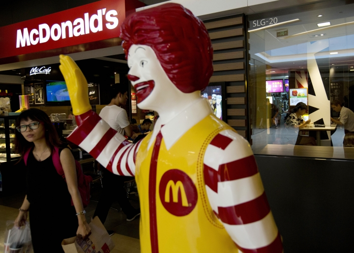 FILE - In this July 31, 2014, file photo, a customer walks past a statue of Ronald McDonald on display outside a McDonald's restaurant in Beijing. Fast food giant McDonald's said in a statement Monday, Jan. 9, 2017 it is selling a controlling stake in its China business to a group of investors led by state-owned Chinese conglomerate Citic in a deal worth up to $2.1 billion. (AP Photo/Andy Wong, File)
