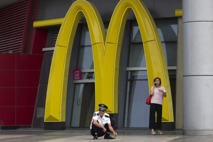 In this photo taken Aug. 2, 2016, a security guard rests near a giant logo for McDonald in northern China's Tianjin Municipality. Fast food giant McDonald's says Monday, Jan 9, 2017 it is selling a controlling stake in its China business to a group of investors led by state-owned Chinese conglomerate Citic in a deal worth up to $2.1 billion. (AP Photo/Ng Han Guan)