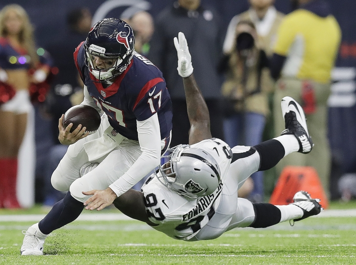 Houston Texans quarterback Brock Osweiler (17) scrambles for a first down against Oakland Raiders defensive end Mario Edwards (97) during the first half of an AFC Wild Card NFL football game Saturday, Jan. 7, 2017, in Houston. (AP Photo/Eric Gay)