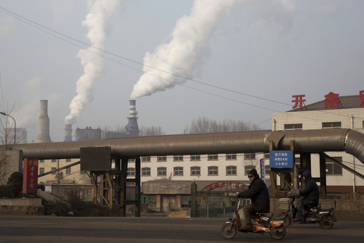 In this photo taken Friday, Dec. 30, 2016, a man rides a bike past smoke spewing from the sprawling complex that is a part of the Jiujiang steel and rolling mills in Qianan in northern China's Hebei province. China's top economic planner pledged Tuesday, Jan 10, 2017, to continue cutting steel and coal production that have been a source of trade friction with many countries. (AP Photo/Ng Han Guan)