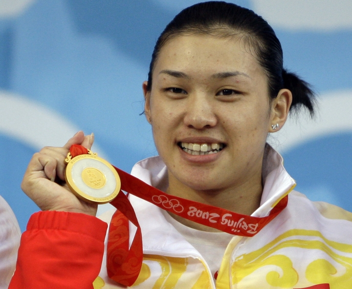 FILE - In this Aug. 15, 2008, file photo, Cao Lei, of China, holds up her gold medal in the women's 75 kg. of the weightlifting competition at the Beijing 2008 Olympics in Beijing, China. IOC has stripped Olympic gold medals from three Chinese women weightlifters for doping at their home 2008 Beijing Games. The IOC says all three Chinese weightlifters tested positive for the banned growth hormone GHRP-2. They were: Cao Lei in the 75-kilogram class; Chen Xiexia in the 48kg class; and Liu Chunhonog at 69kg, it was reported on Thursday, Jan. 12, 2017. (AP Photo/Andres Leighton, file)