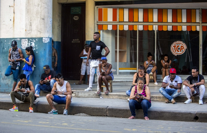 In this Jan. 6, 2017 photo, people use a public wifi hotspot in Havana, Cuba. Home internet came to Cuba in December 2016, in a limited pilot program that's part of the most dramatic change in daily life here since the declaration of detente with the United States on Dec. 17, 2014. (AP Photo/Desmond Boylan)