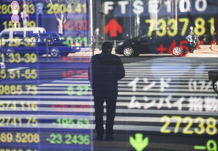 A man is reflected on the electronic board of a securities firm in Tokyo, Monday, Jan. 16 2017. Asian shares were mostly lower Monday morning amid worries about Britain's exit from the European Union, and Takata stock dropped in Tokyo after the air bag maker agreed to a guilty plea in the U.S. over massive recalls. (AP Photo/Koji Sasahara)
