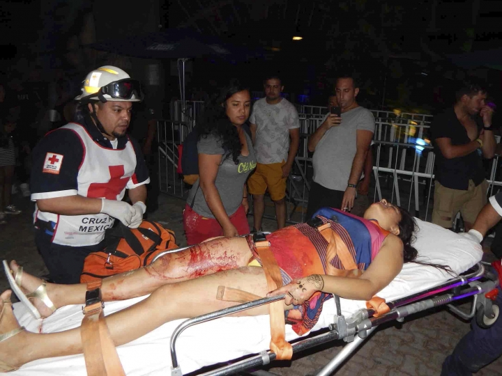 In this photo released by Por Esto de Quintana Roo, a first responder aids a woman wounded after a shooting at an electronic music festival in the Caribbean coast resort of Playa del Carmen, Mexico, early Monday, Jan. 16, 2017. The deadly shooting occurred in the early morning hours outside the Blue Parrot nightclub while it was hosting part of the BPM electronic music festival, according to police. (Por Esto de Quintana Roo, via AP)