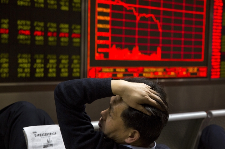 FILE - In this Wednesday, Nov. 9, 2016, file photo, a Chinese man reacts near a board showing the Shanghai Stock Exchange Composite Index at a brokerage in Beijing, China. A board member of the American Chamber of Commerce in China, Lester Ross, says China is preparing to retaliate if U.S. President-elect Donald Trump carries out promises to impose sanctions on Chinese goods. (AP Photo/Ng Han Guan, File)