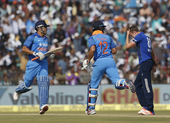 England 's bowler Jake Ball, right, reacts after a delivery as India's Mahendra Singh Dhoni, left, and Yuvraj Singh run between the wickets during their second one day international cricket match at the Barabati Stadium in Cuttack, India, Thursday, Jan. 19, 2017. (AP Photo/Aijaz Rahi)